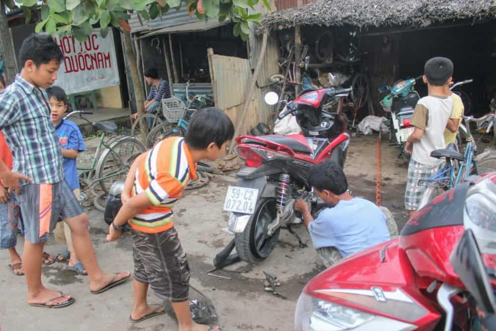Fixing a flat tyre, Mekong Delta